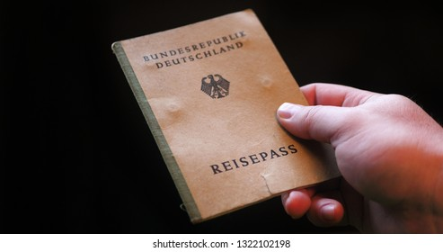 Old german passport from 1955 in the male hand on the borderline. History Concept Idea