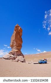 Old german vintage campervan at stone formation Pacana Monks, Monjes De La Pacana, The Indian Stone, near Salar De Tara, Los Flamencos National Reserve, Atacama Desert, Chile, South America