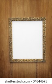 Old gilded photo frame with blank paper on wooden wall