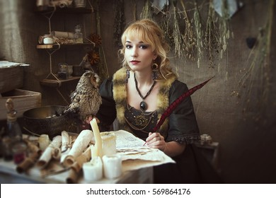 old girl in a dress at a desk with a pen in hand. On a table sits an owl with yellow eyes. Cabinet witches. Fantasy Photo