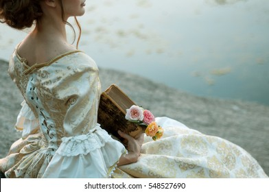 old girl in medieval dress on the river holding a vintage old tattered book and bookmarks bouquet of roses