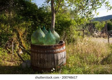 Old glass wine bottles on a wood barrel