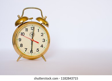 Old gold alarm clock isolated on the white background. Copy space.