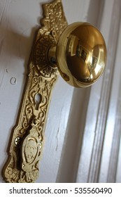 Old gold door knob with reflection of room.