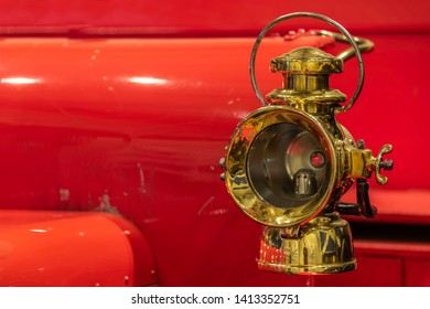 An old gold-coloured carbide lamp against a bright red body.