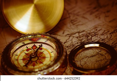 Old golden compass with magnifier and map