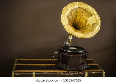 Old golden gramophone with horn speaker stands against anicent background, produces songs recorded on plate. Music and nostalgia concept. Gramophone with phonograph record