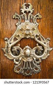 Old golden metal door handle closeup