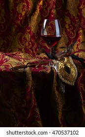Old golden Venetian mask and red wine