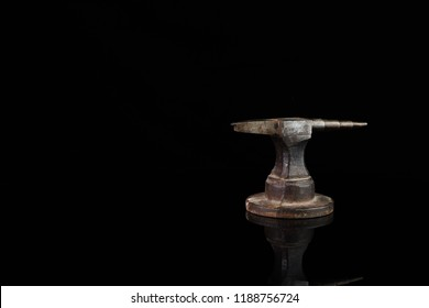 An old goldsmith anvil with a reflection against a black background