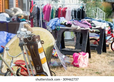 An old golf bag filled with clubs at a yard sale with a jumble of clothing and toys in the soft background