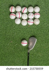 Old golf balls and iron on artificial grass in driving range for practice.