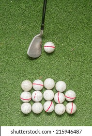 Old golf balls and iron on artificial grass in driving range for swing practice.
