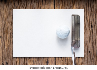 Old golf club (putter) and ball on rough cardboard paper on old wood background