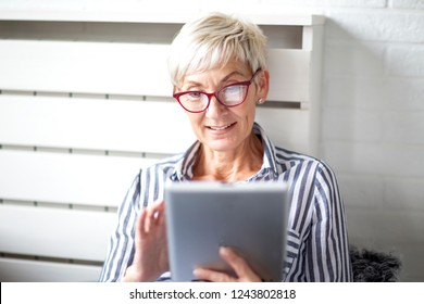 Old good looking woman sitting and use tablet to comunicate with her long distance family