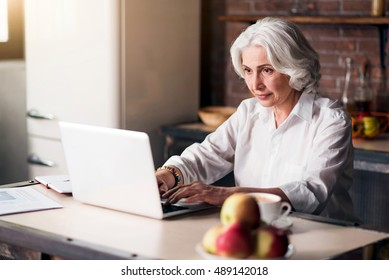 Old good-looking lady using her laptop
