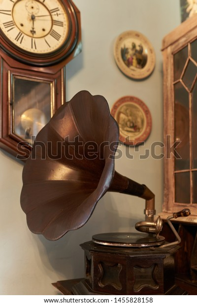 Old gramophone in vintage room setting with a pendulum clock on the wall in the background