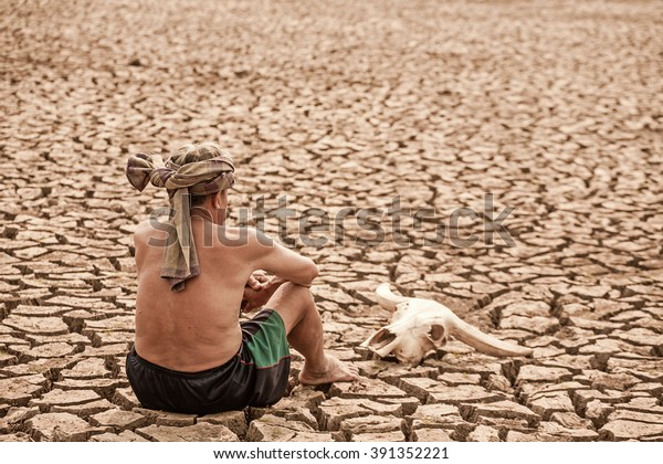 Old grandfather sit down with animal skulls pray for raining on cracks in the dried soil in arid season.