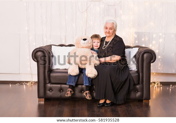 Old grandmother with her grandson sitting on a sofa