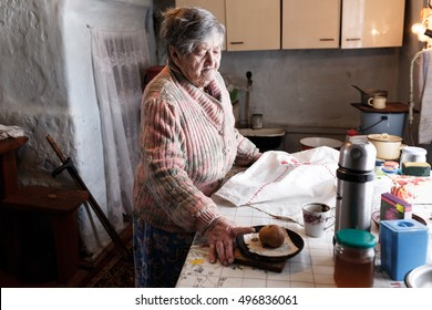 old grandmother in the kitchen of the old house in the village