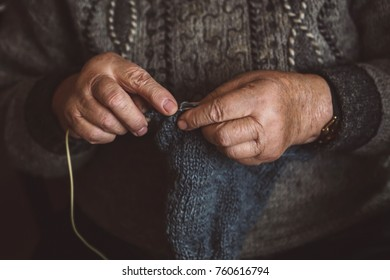 The old grandmother knits warm clothes sitting at the table