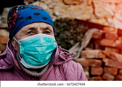 Old grandmother in a mask because of a coronavirus. Deficit of medical masks with an outbreak of a coronavirus. News of the coronavirus. The spread of the new coronavirus across Europe. Deadly corona