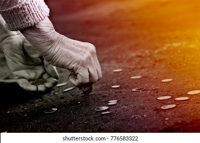 Old grandmother picks up a coin from the road close-up