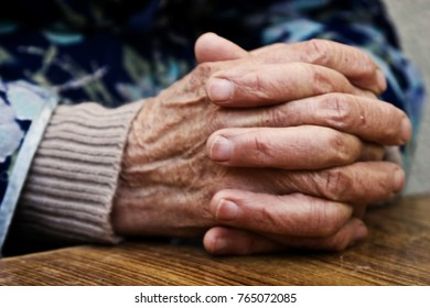 The old grandmother put wrinkled hands on a wooden table