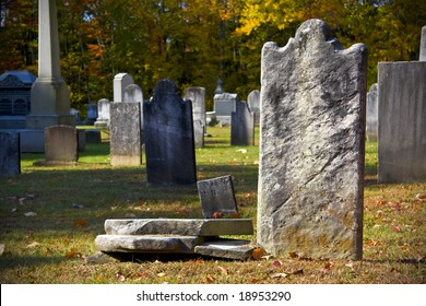 Old granite blank headstone in creepy churchyard during autumn season