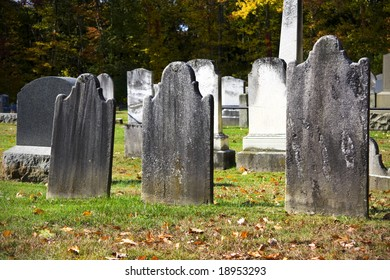 Old granite blank headstones in creepy churchyard during autumn season
