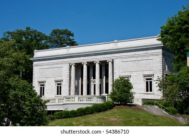 An old granite museum with columns under a blue sky