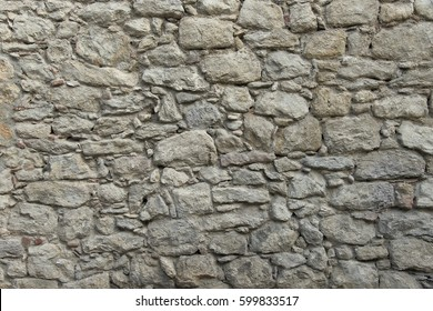 Old granite stone wall texture background close up