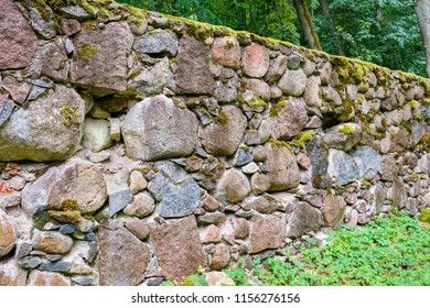 Old granite wall in park, covered with moss and lichen. Alatskivi, Estonia, Europe