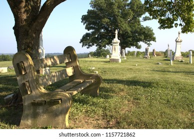 Old grave monuments hover in the background of a rustic, old park bench with no people