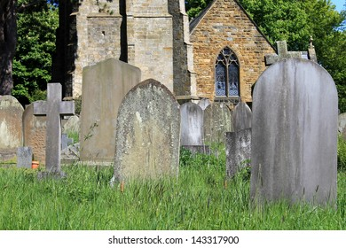 Old graves in cemetery with church in background, England.