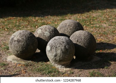Old gray cannonballs lie on the ground