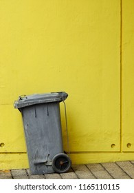 Old gray plastic bin with yellow wall background
