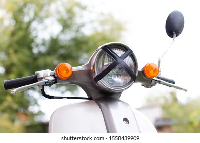 Old gray scooter with broken headlight and black tape cross over headlamp on the blurred background. Close-up.