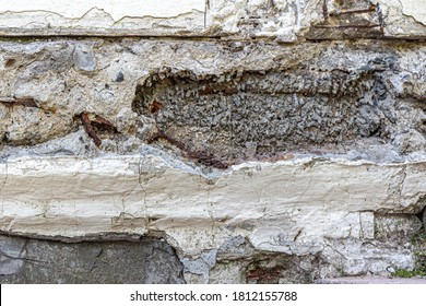 An old gray wall with cracked and crumbling plaster, rusty rebar wire in solidified cement mortar