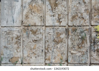 old gray wall tile background with remnants of paper advertising. old tile with peeling paint, abstract