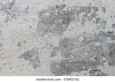 old gray and white concrete wall with crumbling paint. Beautiful textured background for design