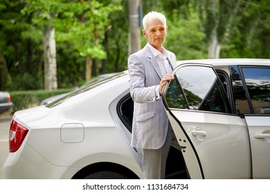 Old gray-haired bussines man in formalwear coming out of the car