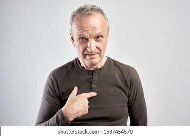 Old gray-haired man points finger at himself, is that for me? Senior citizen with a questioning look in a white studio