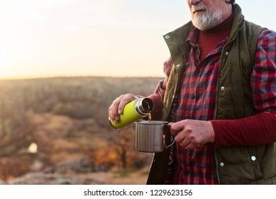 old gray-haired tourist with a beard drinks tea from a thermos in an iron mug against the background of the gorge and stones