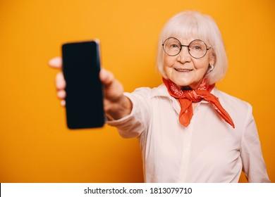 Alte grauhaarige Frau mit grauen Augen, weißer Bluse, orangefarbener Krawatte und runder Brille, die der Kamera das unscharfe Telefon zeigt. Seniorin einzeln auf orangefarbenem Hintergrund und mit Kamera