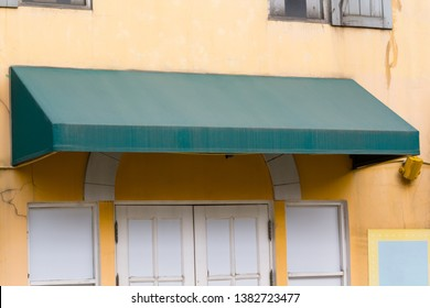 old green awning over the entrance door with blank white sign.