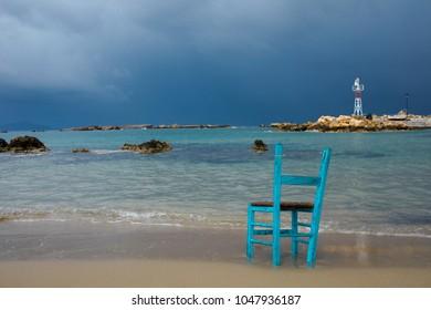 Old green beach chair on sandy beach
