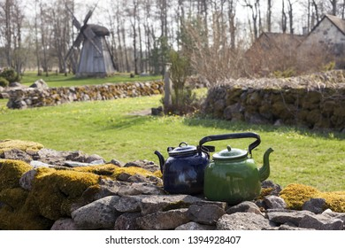 Old green and blue kettle on traditional mossy stone wall on sunny day, wooden post mill and house roofs on background. Photographed in Saaremaa, Estonia, Europe.