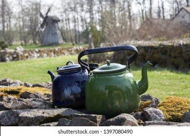 Old green and blue kettles on mossy stone wall on sunny day, old post mill and house roofs on background. Photographed in Saaremaa, Estonia, Europe.