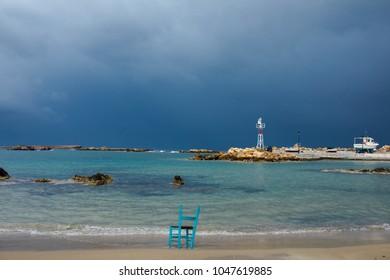 old green chair on sandy beach. Cloudy blue sky above the sea